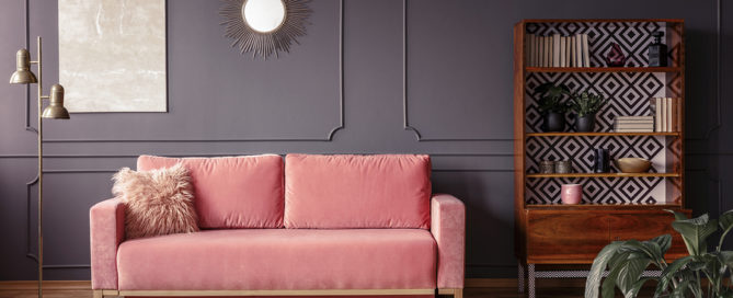 Cushions and blankets on a powder pink velvet sofa in a luxurious gray living room interior with wooden furniture