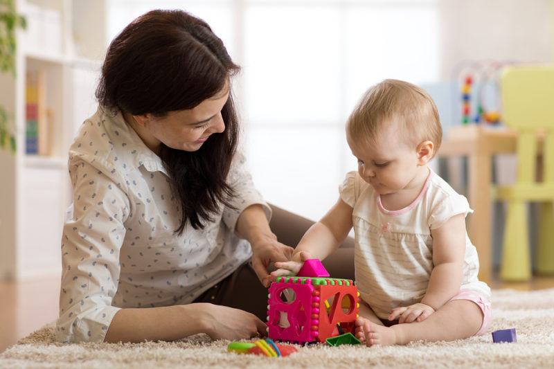 Babysitter looking after baby. Child girl plays with sorter toy sitting on the carpet at home